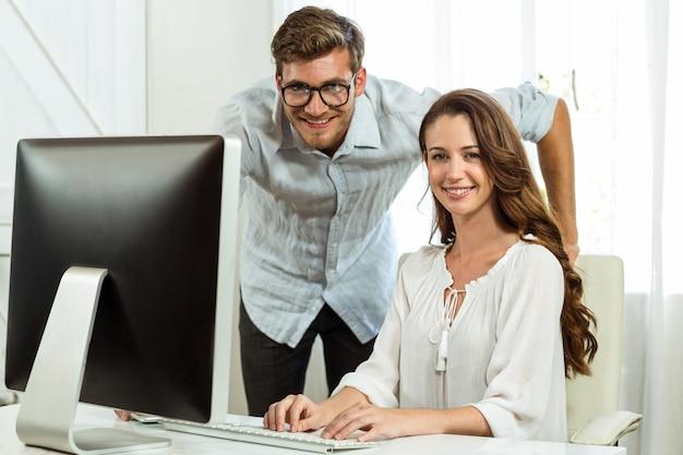 Colegas felizes do retrato usando o computador na mesa de escritório