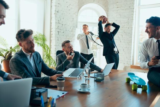 Colegas felizes se divertindo no escritório enquanto seus colegas trabalham duro