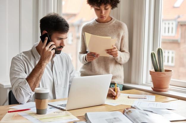 Colegas homem e mulher fazem pesquisas para projeto de inicialização, pose perto da área de trabalho.