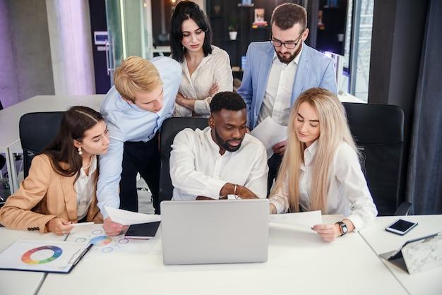 Colegas internacionais masculinas e femininas inspiradas trabalhando juntas em seu projeto conjunto no computador na moderna sala de escritórios.