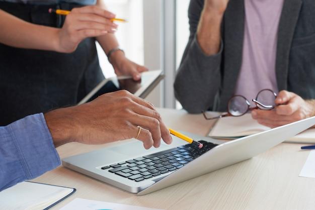 Colegas irreconhecíveis, olhando para a tela do laptop na reunião de trabalho