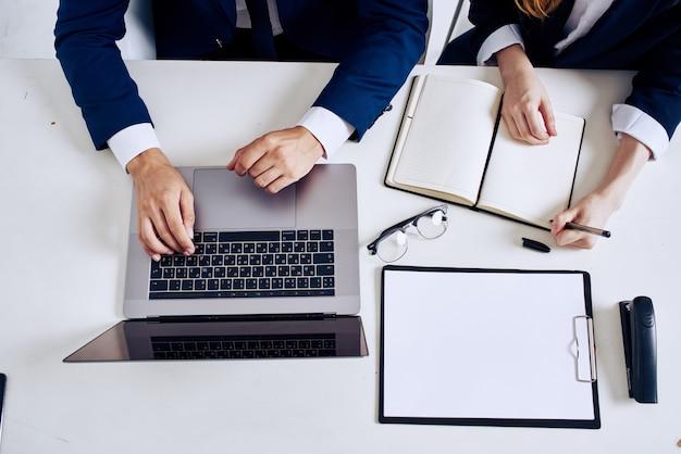 Colegas laptop e documentos na tecnologia de mesa