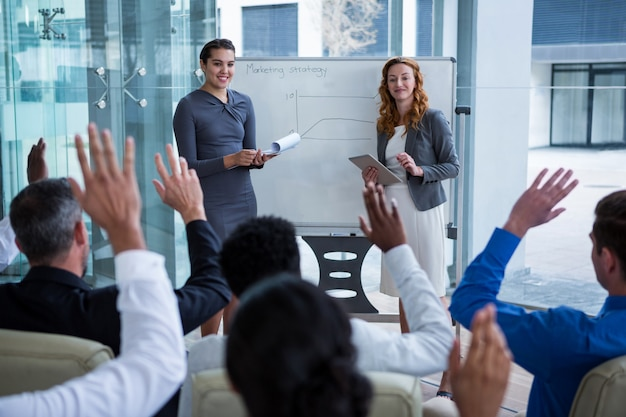 Colegas, levantando as mãos durante a reunião