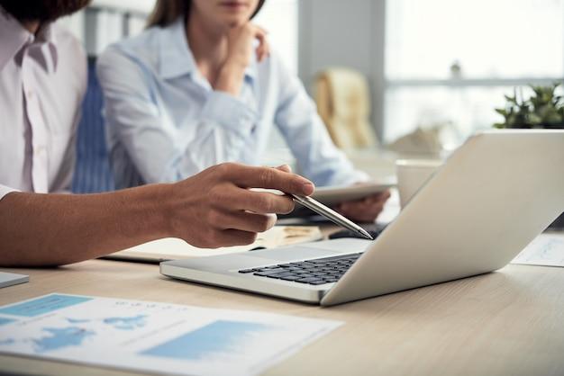 Colegas masculinos e femininos irreconhecíveis, olhando para a tela do laptop no escritório