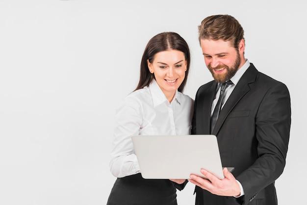 Colegas masculinos e femininos sorrindo e olhando para laptop