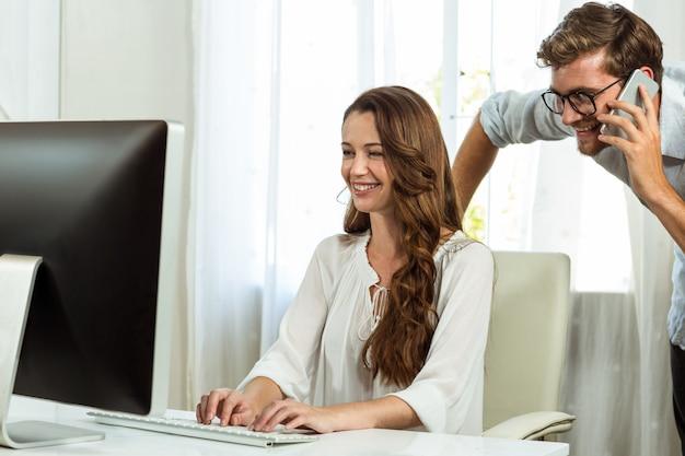 Colegas masculinos e femininos, usando o computador na mesa de escritório