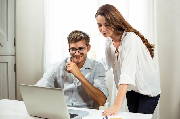 Colegas masculinos e femininos, usando o laptop no escritório