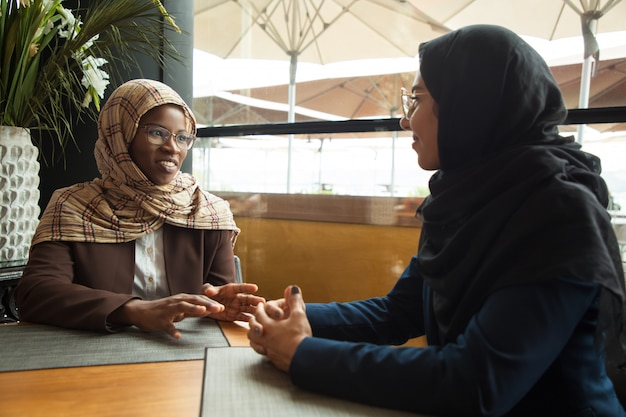 Colegas muçulmanas conversando durante a pausa para o almoço