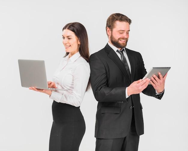 Colegas mulher e homem em pé com dispositivos
