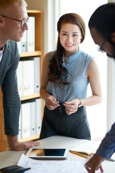 Colegas multiétnicas em pé ao redor da mesa com documentos na reunião de negócios