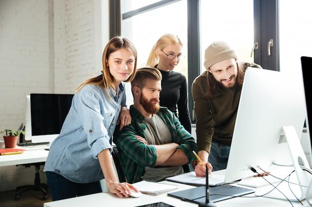 Colegas no escritório, conversando entre si usando o computador.