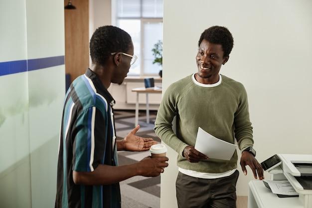 Colegas positivos conversando perto da copiadora durante a pausa para o café no corredor de uma grande empresa