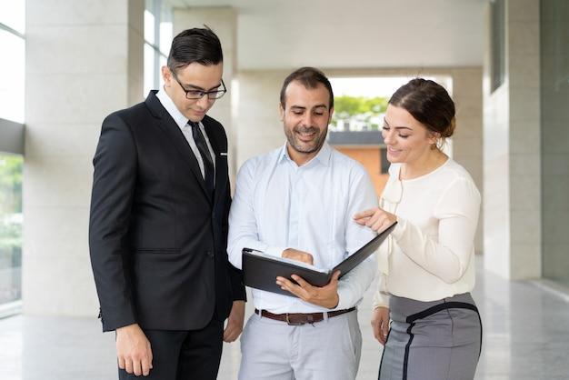 Colegas positivos que discutem termos do contrato de negócios