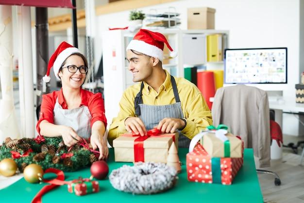 Colegas preparando decoração de natal e embrulhando presentes