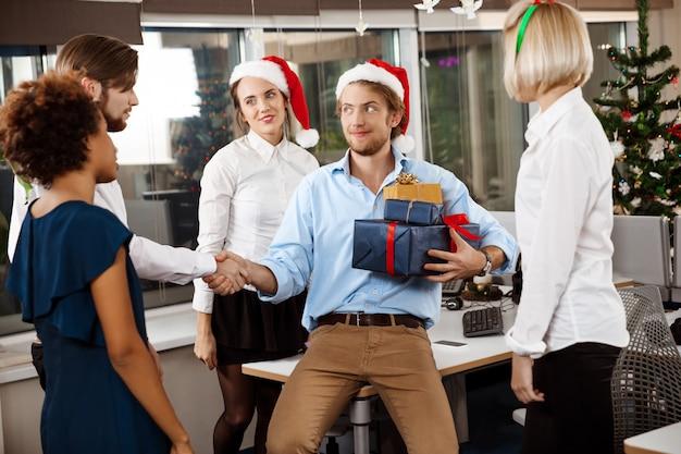 Colegas que comemoram a festa de natal no escritório que sorri dando presentes.
