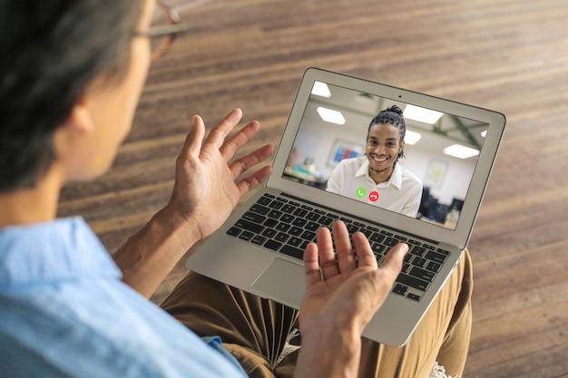 Colegas que têm uma vídeo chamada para respeitar a regra do trabalho a distância social
