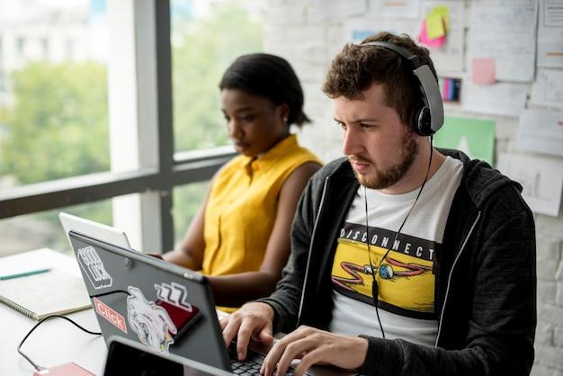 Colegas que trabalham em conjunto com laptop