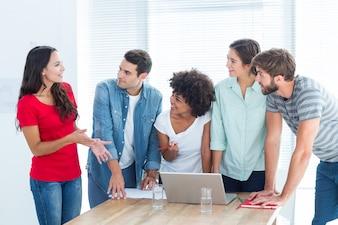 Colegas reunidos em torno de um laptop no escritório