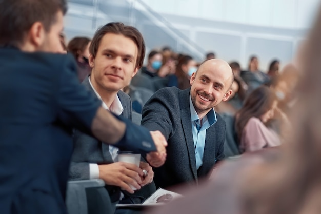 Colegas se cumprimentando antes do início do seminário de negócios