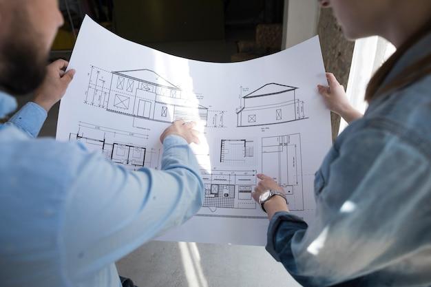 Colegas, segurando, blueprint, e, discutir, ligado, projeto, em, escritório