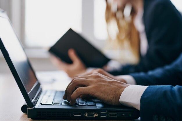 Colegas sentados em frente a um laptop, trabalho em equipe, profissionais da internet