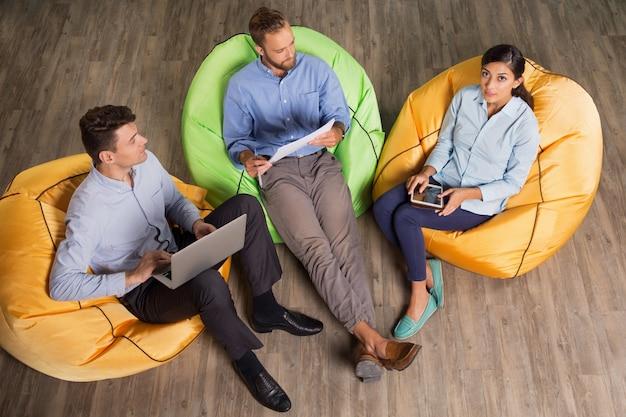 Colegas sentados em pufes e de trabalho