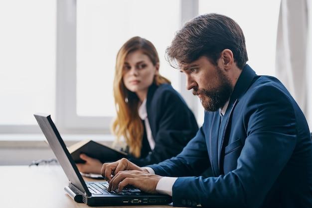 Colegas sentados em uma mesa com um laptop comunicação oficiais de finanças