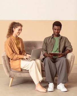 Colegas sentados no sofá e usando um laptop