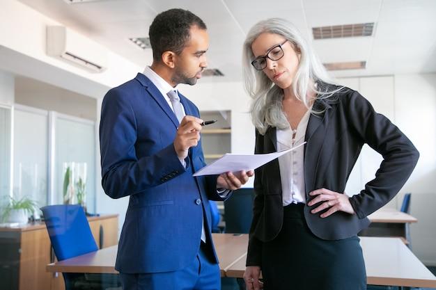 Colegas sérios, discutindo o documento do projeto para assinatura e o gerente feminino de cabelos grisalhos no chefe de escuta de óculos. parceiros trabalhando na sala de reuniões. conceito de trabalho em equipe, negócios e gestão