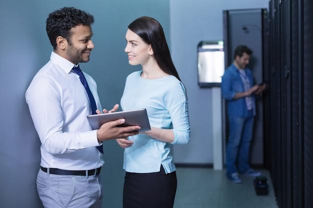 Colegas simpáticos, positivos e alegres segurando um tablet e sorrindo enquanto olham um para o outro