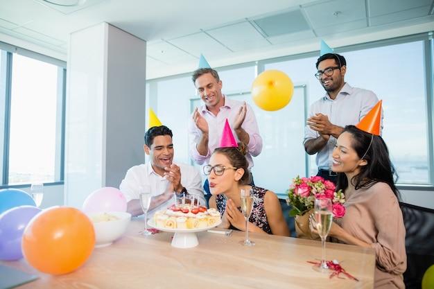 Colegas sorridentes comemorando o aniversário de uma mulher