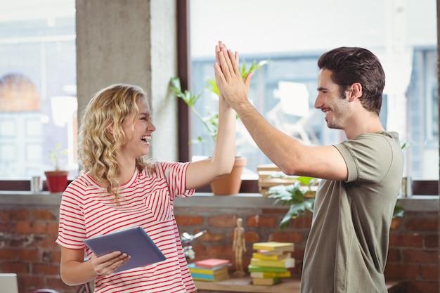Colegas sorridentes fazendo cinco enquanto trabalhava no escritório criativo
