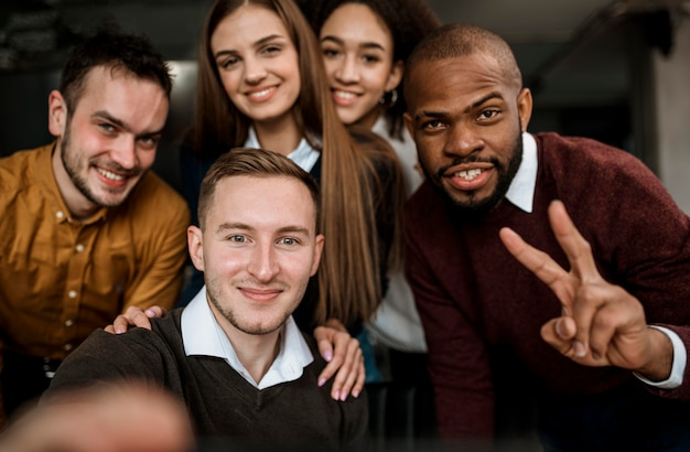 Colegas sorridentes tirando uma selfie antes de uma reunião