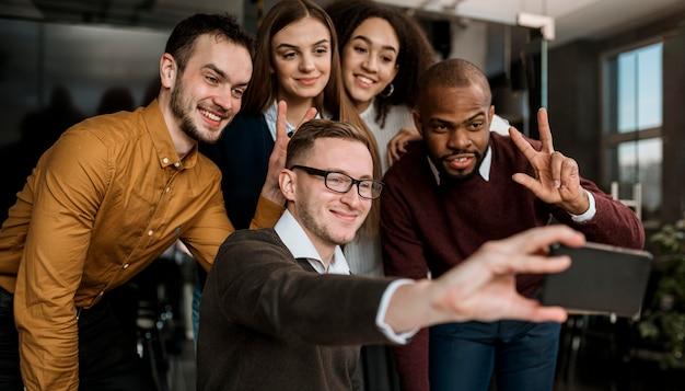 Colegas sorridentes tirando uma selfie durante uma reunião