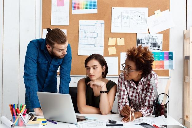 Colegas sorrindo, falando, discutindo desenhos, novas idéias no escritório