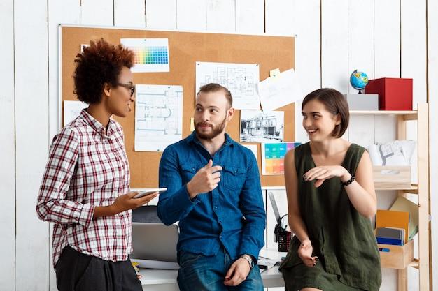 Colegas, sorrindo, falando, discutindo novas idéias no escritório