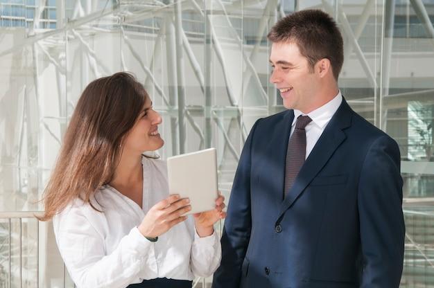 Colegas sorrindo, mulher mostrando dados sobre tablet
