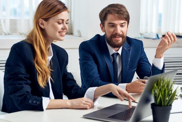 Colegas trabalham juntos na frente da tecnologia de laptop de escritório