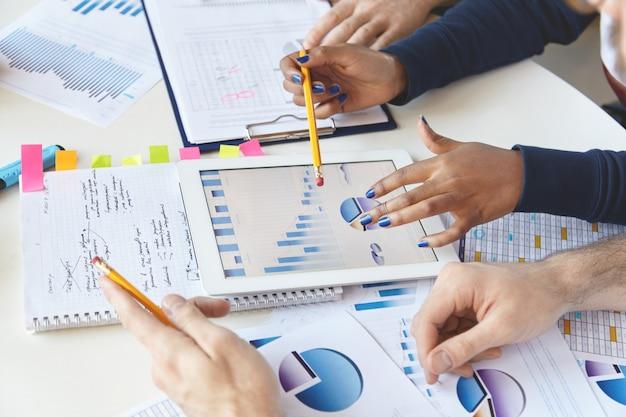 Colegas trabalhando juntos em relatórios financeiros usando um gadget moderno.