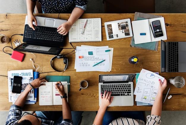 Colegas trabalhando juntos em uma mesa em laptops
