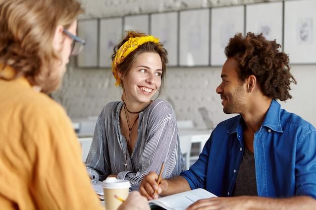 Colegas trabalhando juntos enquanto estão sentados em um café