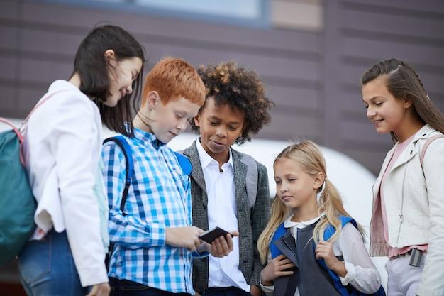 Colegas, usando telefone celular ao ar livre