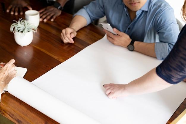 Colegas usando um papel branco em branco no escritório