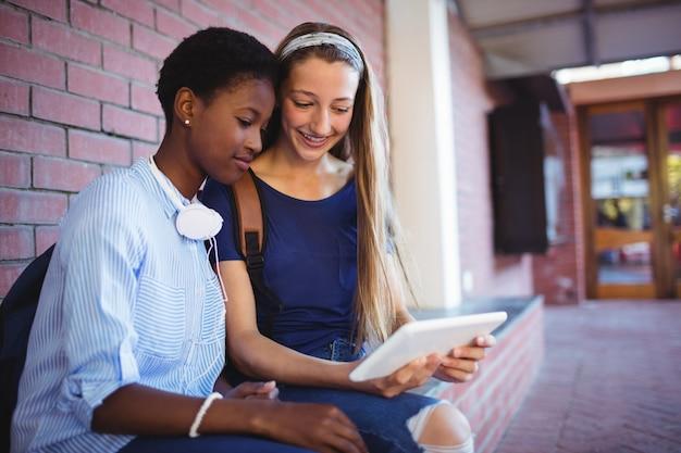 Colegiais sentadas contra uma parede de tijolos usando tablet digital