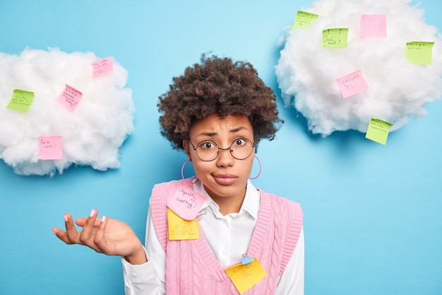 Colegial afro-americana hesitante e sem noção posa em torno de adesivos de papel com tarefas escritas a fazer, usa postá-la para novas ideias usa óculos redondos camisa branca colete rosa