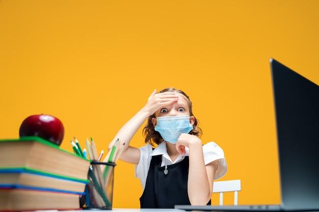 Colegial assustada com máscara protetora está doente e segura a cabeça com a mão no ensino à distância