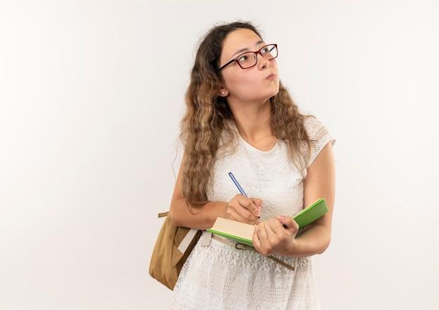 Colegial bonita jovem pensativa de óculos e bolsa nas costas, escrevendo no livro, olhando para o lado isolado na parede branca