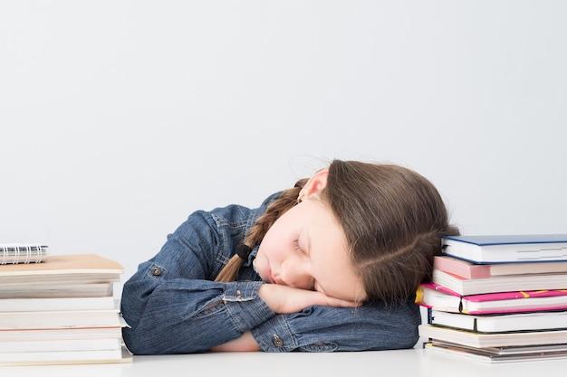 Colegial cansada dormindo em sua mesa durante a aula