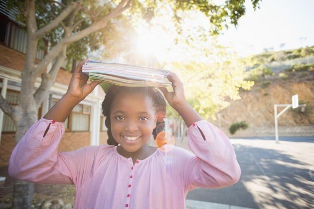 Colegial carregando livros na cabeça