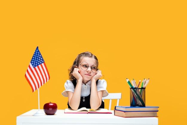 Colegial caucasiana entediante e triste de óculos estudando em casa, aula de inglês, bandeira dos eua